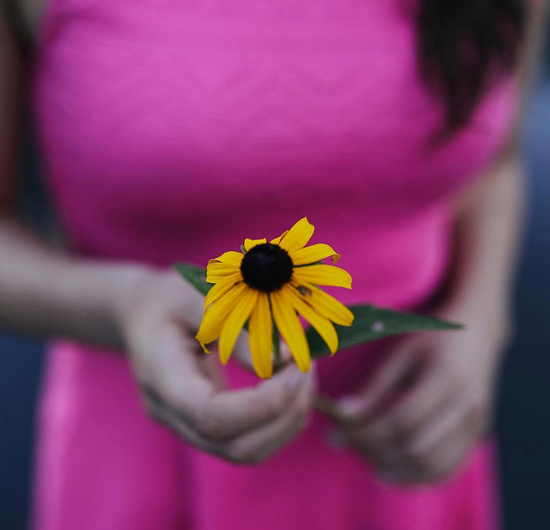 woman holds flower
