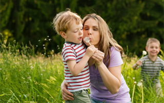 mom blowing bubbles with boy